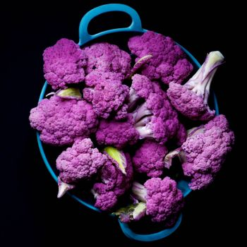 Fresh Raw Purple Sprouts of Cauliflower with Leafs in Blue Bowl isolated on Black background. Top View