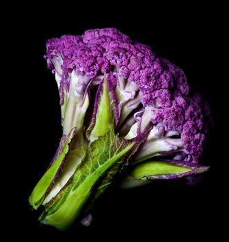 Fresh Raw Purple Cauliflower with Leafs isolated on Black background