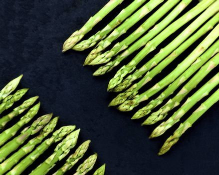 Borders of Fresh Asparagus Sprouts closeup on Black Slate background