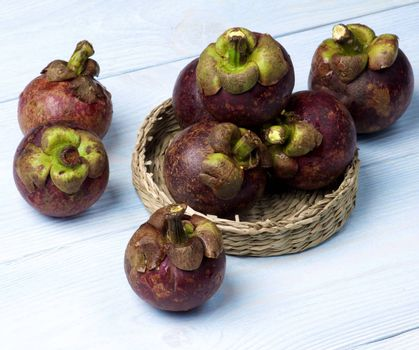 Stack of Fresh Ripe Mangosteen in Wicker Bowl closeup on Light Blue Wooden background