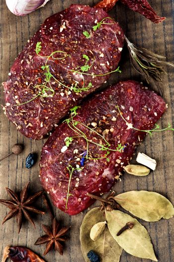 Two Marinated Raw Boneless Beef Steaks with Spices, Garlic, Chili Pepper and Greens closeup on Wooden Cutting Board. Top View