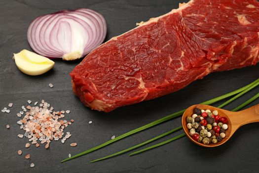 Raw beef steak meat cut and spices on black board