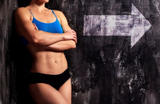 Muscular woman on a dark background with white arrow sign