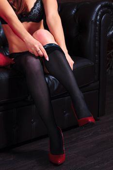 Sexy woman puts on stockings. Beautiful lady