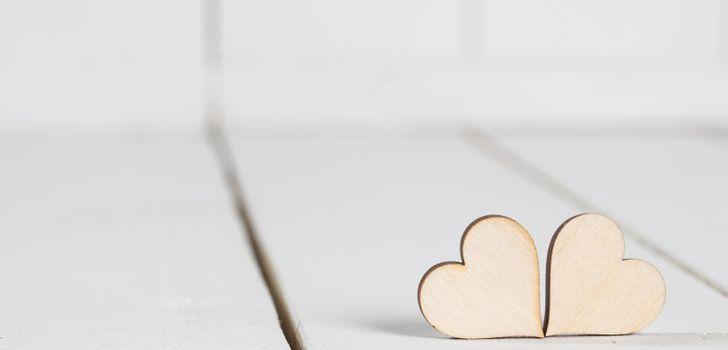Two wooden Valentine day hearts on white wooden background