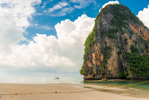 Beautiful clouds, high cliff and a small yacht in the sea, Thailand