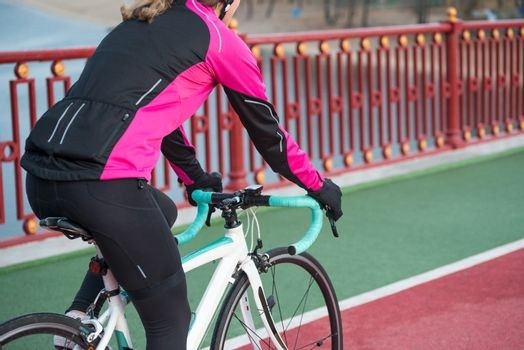 Young Woman in Bright Pink Jacket Riding Road Bicycle on the Bridge Bike Line in the Cold Sunny Autumn Day. Healthy Lifestyle Concept.
