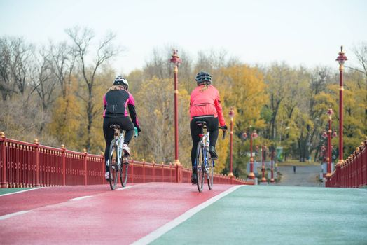 Two Young Female Cyclists Riding Road Bicycles on the Bridge Bike Line in the Cold Autumn Day. Healthy Lifestyle Concept.