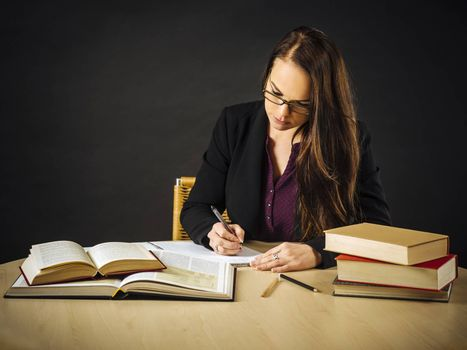 Attractive teacher sitting at her desk writing