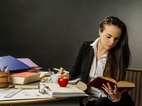 Beautiful teacher sitting at her desk reading