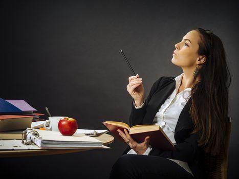 Beautiful teacher sitting at her desk thinking