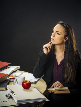 Teacher sitting at her desk thinking