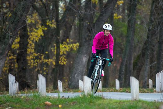 Young Woman in Bright Pink Jacket Riding Road Bicycle in the Park in the Cold Autumn Day. Healthy Lifestyle Concept.