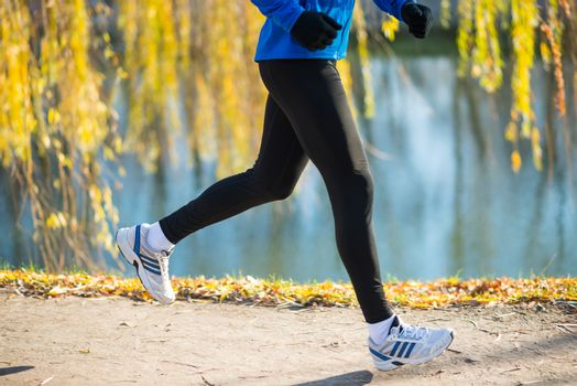 Young Sports Man Running in the Park in Cold Sunny Autumn Morning. Healthy Lifestyle and Sport Concept.