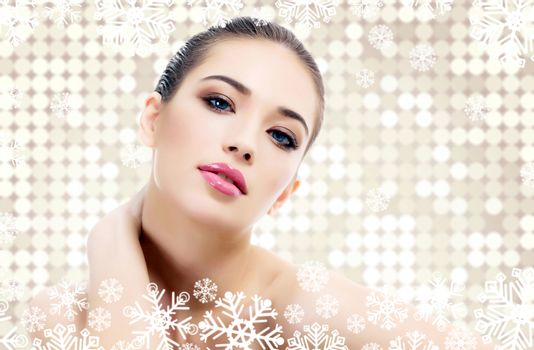 Pretty woman against an abstract background with circles and snowflakes. Winter skin treatment concept