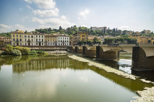Scenic view of the Lungarno at historic center of Florence, Italy. Facades of old medieval houses on waterfront of the Arno River. Florence is a popular tourist destination of Europe.