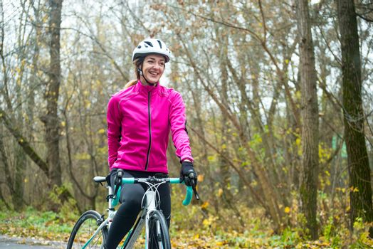 Portrait of Young Smiling Female Cyclist in Bright Pink Jacket Resting with Road Bicycle in the Cold Sunny Autumn Day. Healthy Lifestyle Concept.