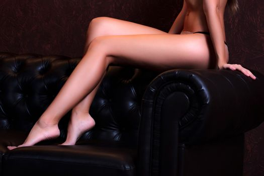 Sexy woman with long slim legs sitting on a dark brown leather sofa