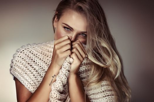 Fashion woman portrait, gorgeous sexy female with big knitted scarf over beige background, conceptual photo of a keeping secrets