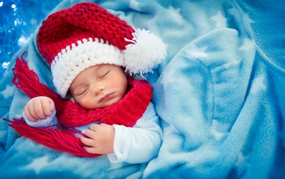 Cute baby boy sleeping in Santa hat