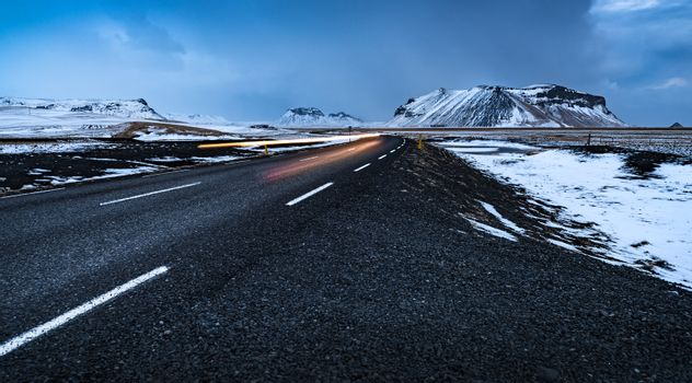 Beautiful winter landscape, empty highway with snowy roadside around it, wintertime road trip vacation in Iceland