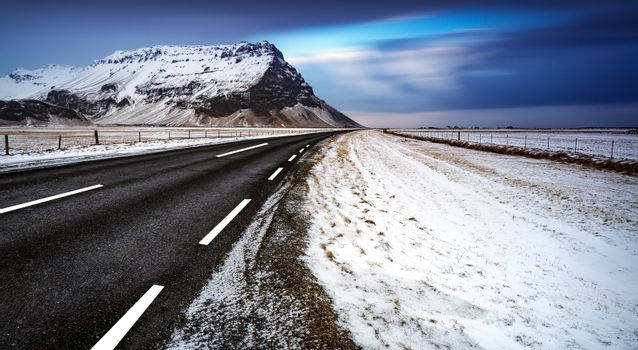Beautiful winter landscape of a road, empty highway, peaceful view on the great mountain covered with snow, wintertime in Iceland