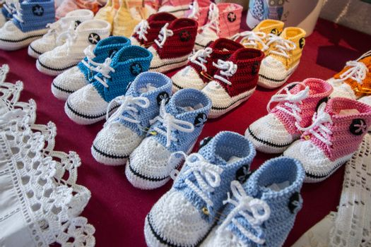 Varied mix of colorful knitted baby shoes.