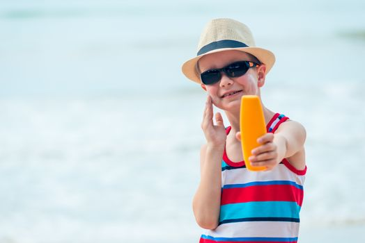 A 7 year old boy shows a protective sun cream and smears his ski