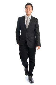 Full body Asian businessman walking