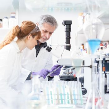 Health care researchers working in life scientific laboratory. Female research scientist and senior male supervisor looking focused at tablet computer screen evaluating and analyzing microscope image.