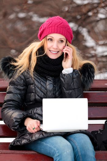 Portrait of smiling woman sitting on a bench in a park talking on cell phone and using laptop.