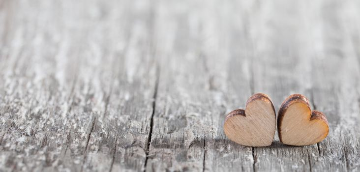 Two small wooden hearts on old cracked wood background