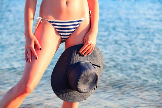 Closeup shot of slim woman with big sunhat. Beach holidays concept.