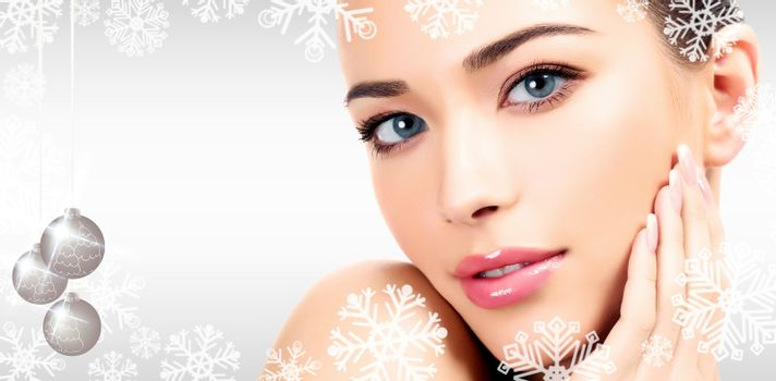 Closeup headshot portrait of a beautiful woman with beauty face and clean smooth soft skin, mild makeup. Grey steel background with snowflakes, christmas baubles and a place for your information