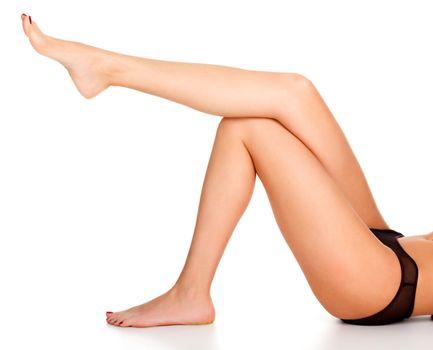 Closeup shot of long beautiful female legs. Woman with slim legs posing on white background