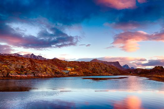 Beautiful landscape of Kabelvag, amazing view of a mountains in sunset light which reflecting in the lake, gorgeous nature of fisherman's town, Norway