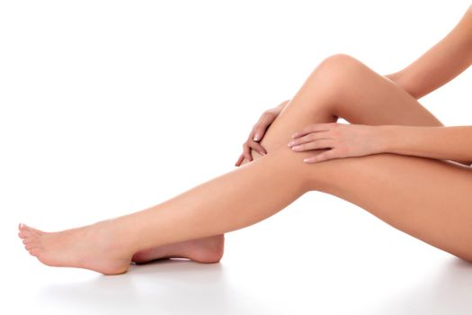 Closeup shot of beautiful female legs and hands. Woman touches her smooth skin with french manicured hands. Isolated on white background