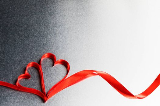 Two red ribbon hearts on metal background with copy space