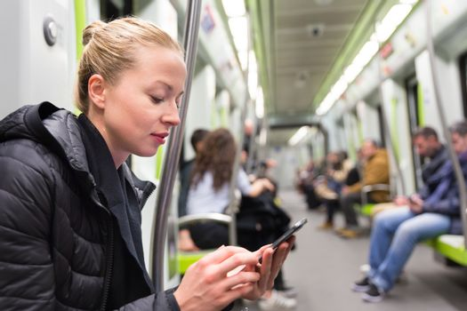 Cheerful young girl texting on mobile phone social network applications while traveling on metro. Wireless internet on public transport concept.