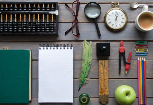 Blank notepad inbetween various items, including stationery and vintage,  laid out on a wooden background