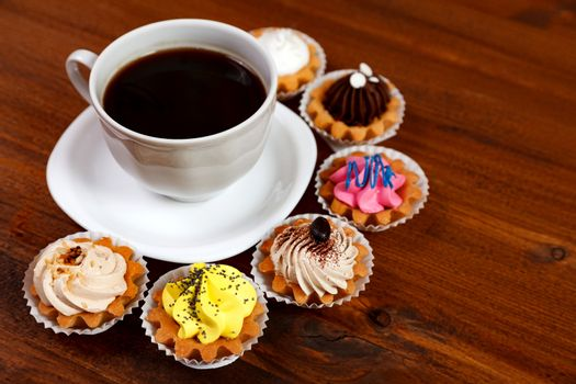 Closeup shot of small cup of coffee with colorful cupcakes