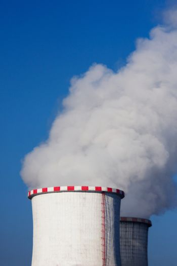 White thick steam out of large chimneys on a power plant