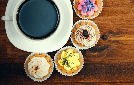 Closeup shot of small cup of coffee with colorful cupcakes. Flat lay style