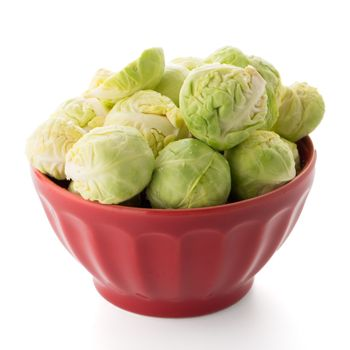 Fresh brussels sprouts on red ceramic bowl isolated on white background.