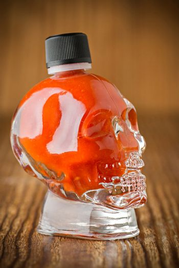 Hot chili sauce in a skull shaped glass on wooden background
