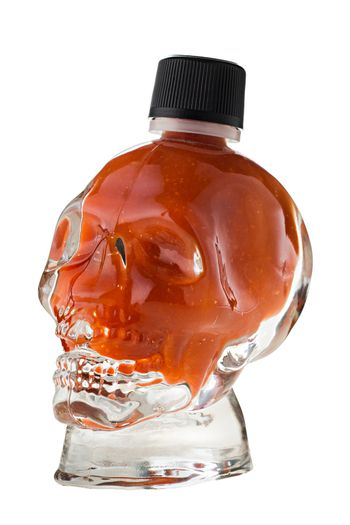 Hot chili sauce in a skull shaped glass on white background