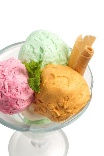 Glass bowl of various colorful ice cream balls with mint leaves and vanilla sticks isolated on white background. From side view.