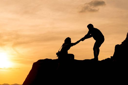 Couple hiking help teamwork and trust silhouette in mountains, sunset and ocean. Male and woman hiker helping each other on top mountain looking
