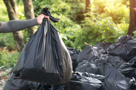 Man Taking Out Garbage In Bags