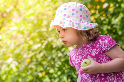 Cute little girl holding half eaten apple